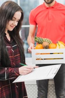 Femme confirmant la livraison de fruits