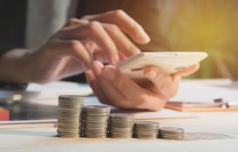 Femme d'affaires à l'aide de la calculatrice avec indices financiers boursiers avec pièce de pile.