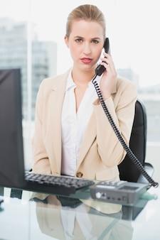 Femme d'affaires fronçant les sourcils répondant au téléphone
