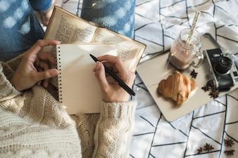 Femme de culture prenant des notes près de la caméra et de la nourriture du petit-déjeuner