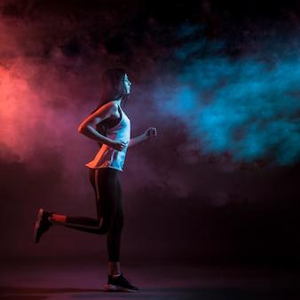 Femme en cours d'exécution dans un studio sombre