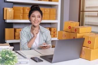 Femme entrepreneur pensant et utilisant une tablette et une boîte à colis, commerce en ligne