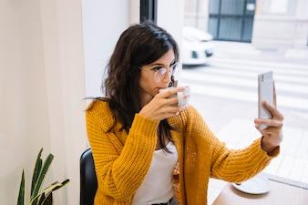 Femme faisant la photo d'elle-même au café