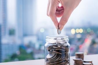 Femme main mettre pièce dans verre de bouteille pour économiser de l'argent