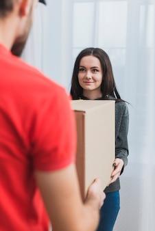 Femme recevant un colis avec un courrier