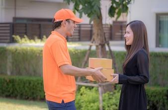 Femme recevant une boîte de livraison du livreur