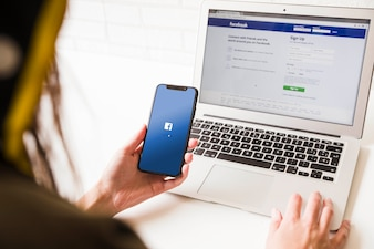 Femme regardant le téléphone mobile avec la page d'accueil de l'application facebook