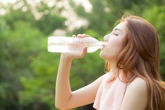 Femme s'asseoir et boire après l'exercice.