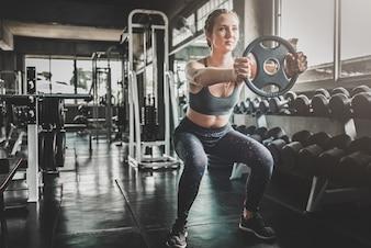 Femme, séance entraînement, poids, plaque, gymnase