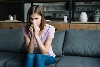 Femme souffrant de nez froid avec du papier de soie