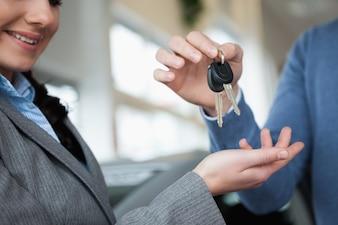 Femme souriante recevant des clés d'une main dans un magasin de voiture