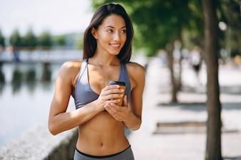 Femme sportive, boire du café dans le parc