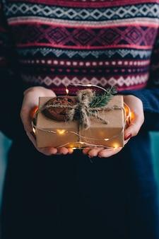 Femme tenant le cadeau de Noël décoré de brins de sapin, cookie et lumières de Noël.