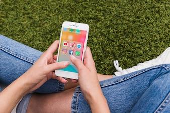 Femme tenant mobile en utilisant les applications de réseaux sociaux