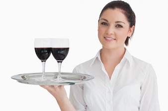 Femme tenant un plateau avec des verres de vin rouge