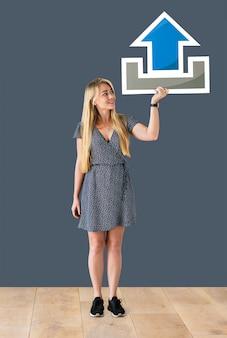 Femme tenant une icône de téléchargement dans un studio