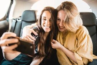 Femmes gaies prenant selfie en voiture