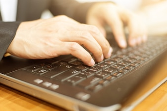 Fermer la main de l'homme d'affaires en tapant le clavier sur ordinateur portable. concept d'affaires et de la technologie.