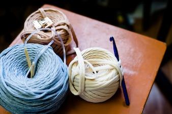 Fil à trois bobines avec crochet à tricoter sur une chaise en bois