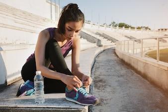 Fille attacher ses chaussures de sport à côté d'une bouteille d'eau