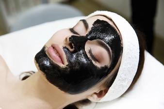 Fille avec un masque noir se trouve sur la table dans le salon de spa