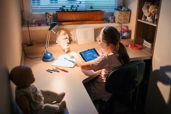 Fille jouant le jeu de la tablette à table