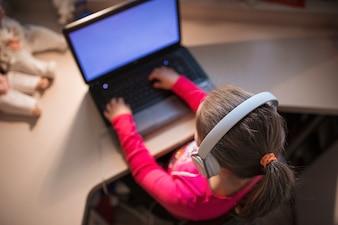 Fille méconnaissable utilisant un ordinateur portable
