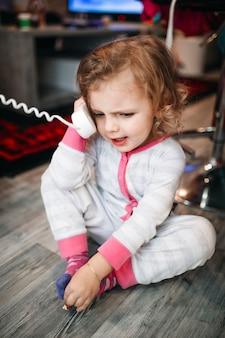 Fille parlant au téléphone au sol