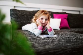Fille pensive avec tablette en regardant la caméra