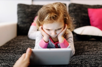 Fille réfléchie, regarder la vidéo sur une tablette