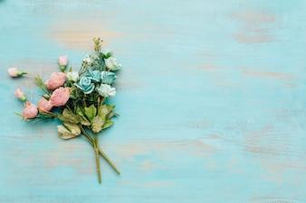 Fleurs bleues et roses avec un fond en bois vintage.