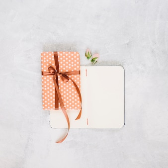 Fleurs et cadeau près de cahier vide