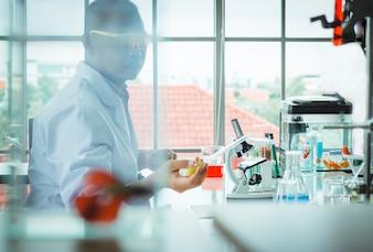 Floue de l'homme asiatique scientifique dans le laboratoire laissant tomber le liquide du bécher