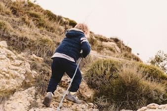 Garçon utilisant une corde pour grimper une petite montagne