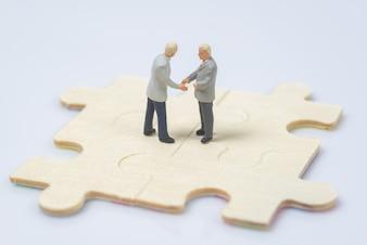 Gens miniatures d'affaires se serrant la main sur le morceau de puzzle