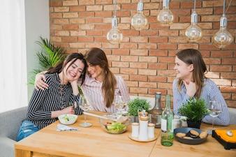 Girlfriends étreindre assis à table