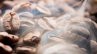 Grains de café rôtir avec de la fumée, mise au point sélective