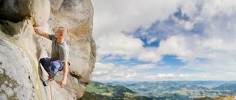 Grimpeur mâle escalade gros rocher dans la nature avec une corde