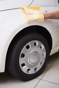 Gros plan d'un homme nettoyant sa voiture dans une nouvelle salle d'exposition
