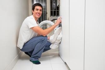 Gros plan d'un jeune homme souriant, mettant des vêtements dans la machine à laver