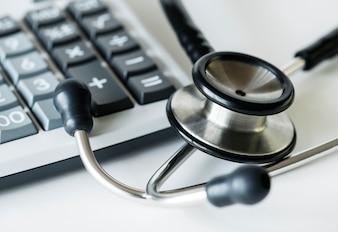Gros plan d'une calculatrice et d'un concept de soins de santé et de dépenses stéthoscope