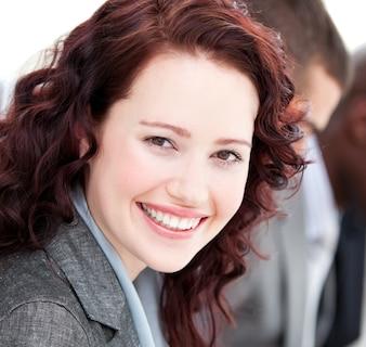 Gros plan d'une femme souriante souriant à la caméra lors d'une réunion