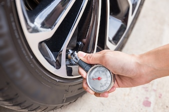 Gros plan d'une main tenant un manomètre pour mesurer la pression d'un pneu de voiture