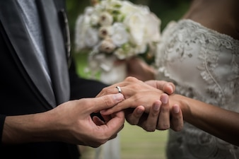 Gros plan du marié porte la bague mariée au jour du mariage. Amour, heureux mariage concept.
