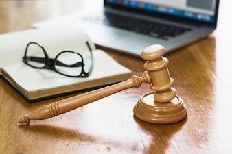 Gros plan du marteau livre; ordinateur portable et lunettes sur un bureau en bois