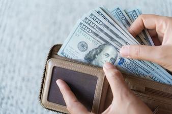 Gros plan Femme Mains prenant l'argent Billets de dollars américains du portefeuille.