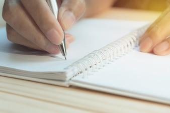 Gros plan main écrit sur papier. Bouchent les gens qui écrivent sur papier.