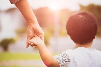Gros plan mère tenant la main d'un enfant. Notion de jour de famille et de mères.