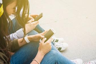 Groupe d'amis assis à l'extérieur en utilisant un smartphone