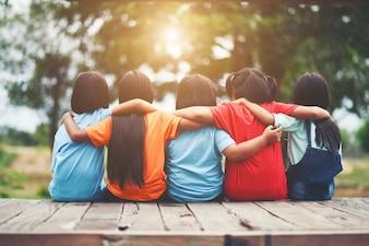 Groupe d'amis enfants bras autour assis ensemble